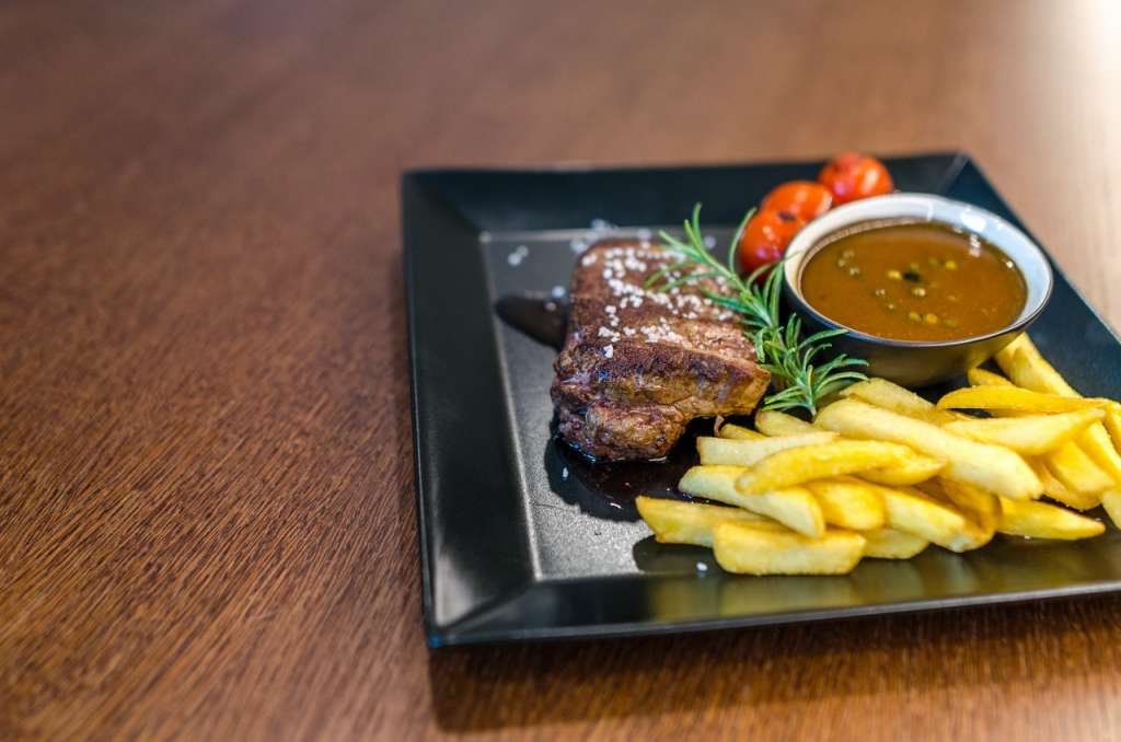 grilled beef with fries and sauce on black ceramic plate 1352264